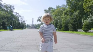 Little boy running along the city street. Slow Motion. Happy child runs to the camera in the park outdoors.