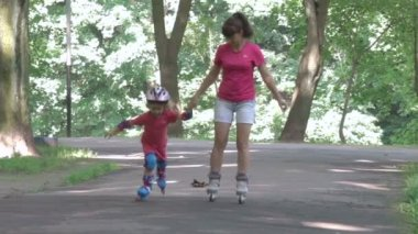 Family, young mother and daughter ride in a roller-skating park. A little girl and young woman in a helmet and defense skates on roller skates. The child rolls on the rollers in the park.