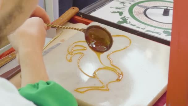 The confectioner draws liquid caramel. The cook makes candy from caramel by hand.