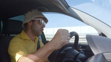 Man driving car, dancing and listening to music. Man singing and dancing happy driving car in city. Crazy men driving a car. Guy in a hat and sunglasses.Slow motion.