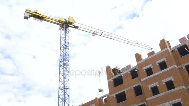 Staveniště s pracovníky výškové domy z cihel věžových jeřábů. Staveniště, budování bytů. Stavební jeřáb pracuje na staveništi, zvýšit cihly, betonové desky.