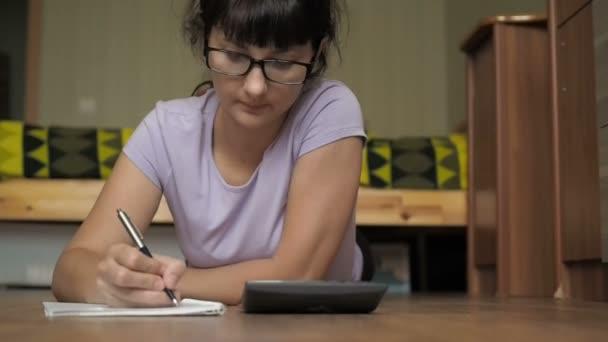 junge Frau mit Brille mit Notizbuch und Taschenrechner, die im College studiert. Geschäftsfrau arbeitet mit Taschenrechner. Haushalt, Finanzen - Frau mit Papieren und Taschenrechner, die zu Hause Geld zählt