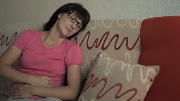 Mladá žena v bolesti ležet na gauči doma. Dívka trpí bolest žaludku a stěžuje si, sedí na pohovce. Menstruace zácpa průjem