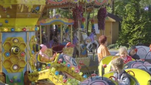 Překrásně barevné včely usmívající se merry Přejít kolo. Malé veselé děti jezdit na kolotoč v dětském zábavním parku. Kaliningrad - září 2017 Rusko