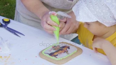 Little children put a multicolored custard on ginger biscuits.