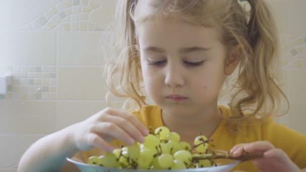 kleines Mädchen isst Trauben von einem Teller, der an einem Tisch sitzt.