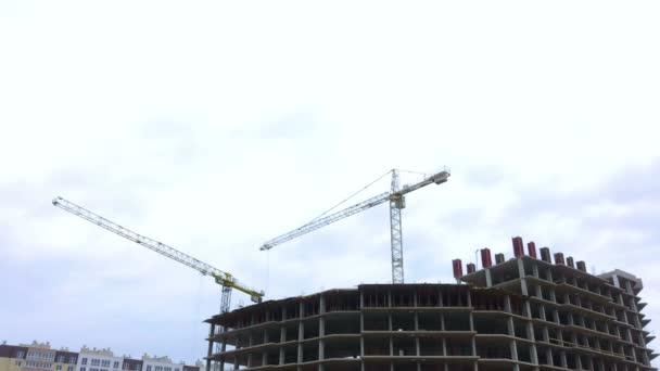 Staveniště s pracovníky výškové domy z cihel věžových jeřábů. Časová prodleva. Stavební jeřáb pracuje na staveništi, zvýšit cihly, betonové desky.
