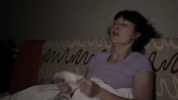 Junge kranke Frau niest nachts zu Hause auf der Couch. Mädchen laufende Nase und Haltungsgewebe, Grippe-Symptome. Gesundheitswesen und medizinisches Konzept. Erkältungen sind der grippale Infekt.