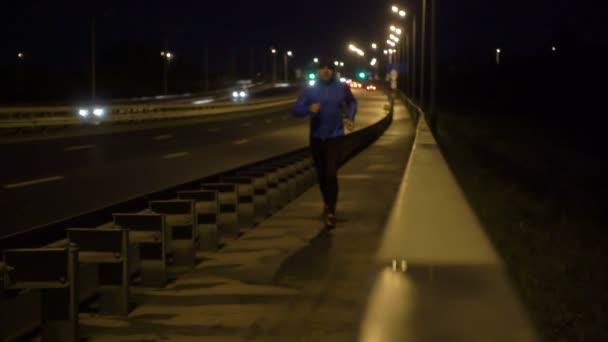 Kondiční sportovce v noci venku po most. Muž v sportovní oblečení je spuštěn ve večerních hodinách. Muž se zabývá fitness, kolem auta.