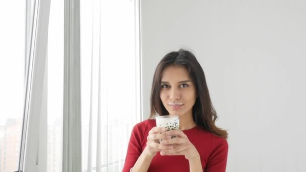 Mladé krásné štíhlé sportovní žena pití jogurt a usmívá se na kameru
