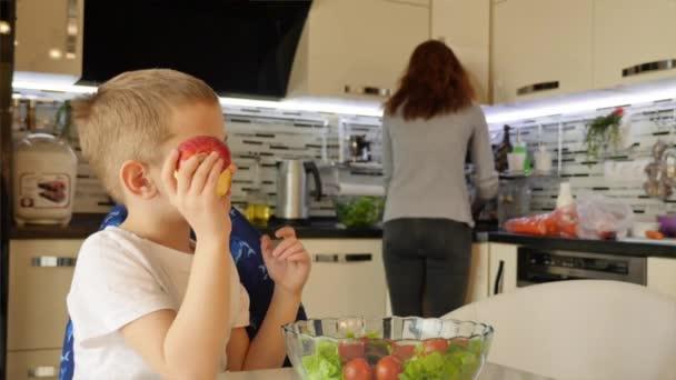 Kluk sedí u stolu. On jí jablko