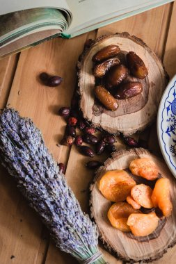 book and dried fruits on wooden plates