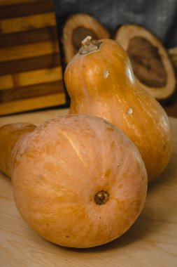 Two pumpkins on wooden table. against the backdrop of  coasters