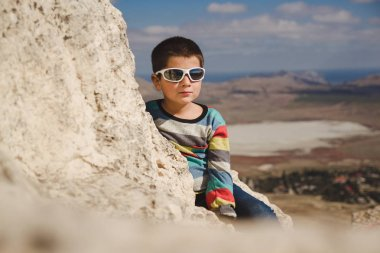 boy in sunglasses sits on the top