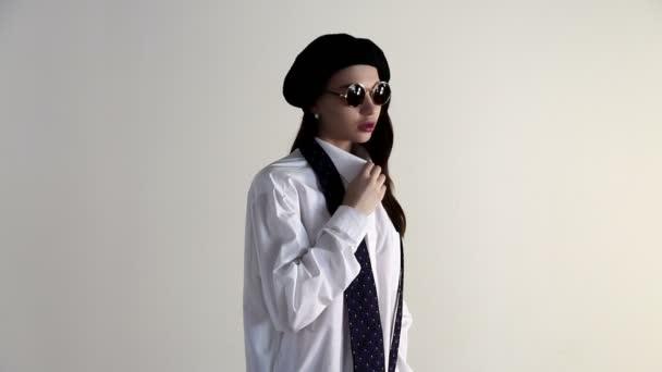 Mladá žena v košili, sluneční brýle a baret pózuje na bílém pozadí