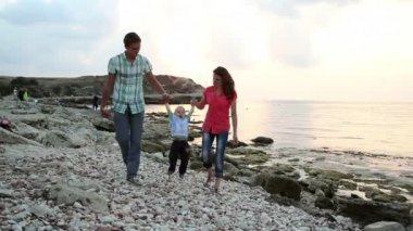 A family walking on a beach.