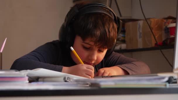 Chlapec ve velkých sluchátek je psaní domácích úkolů