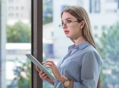 closeup of happy woman in glasses using tablet pc in office