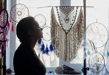 Silhouette of a woman against the window. Behind it hang dreamcatchers, macrame panels, glasses and flowers on the windowsill