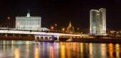 Orosz fehér ház (az Orosz Föderáció kormánya) és a kölcsönös gazdasági segítségnyújtás (KGST) éjjel Moszkvában Tanács egykori háza. Színes megvilágítás és reflexiók a folyón. Moscow, Oroszország