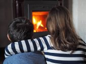 Fotografie little girl and little boy warm up by the fireplace