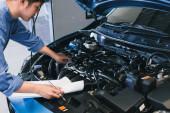 Asijský člověk mechanik inspekce psaní poznámky na schránce.Blue car