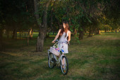 girl in a white skirt and a vest with a bicycle and a basket full of flowers in the park in the evening
