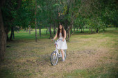 Girl in a white dress rides a bicycle through the park in the evening.
