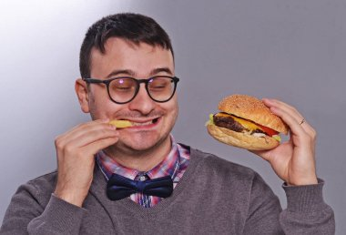 Expressive nerd eating burger