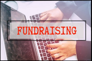 Hand and text FUNDRAISING with vintage backgound. Technology concept.