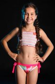 Photo Portrait of a happy young teenage girl in a swimsuit. Pretty child with dark hair and beautiful face adorably smiles. Slender preteen in a bikini.