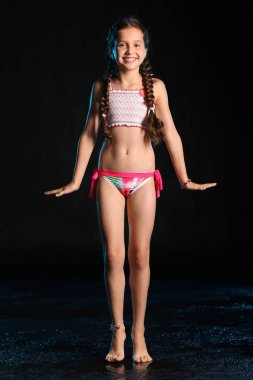 Happy young teenage girl in a swimsuit stands barefoot on a black background. Pretty child with dark hair and beautiful face adorably smiles. Slender preteen in a bikini.