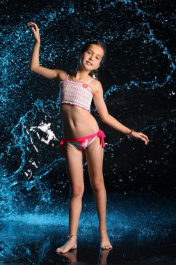 Adorable young teenage girl in a swimsuit stands barefoot in splashing water. Pretty child with dark hair, beautiful face and a slim figure. Slender preteen in a bikini.