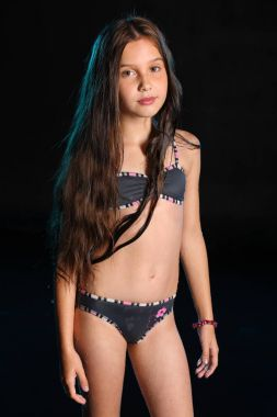 Attractive pretty young teenage girl posing in a wet bikini. The child with long chic dark hair and a beautiful slender body. Lovely pre-teen female stands in swimsuit.