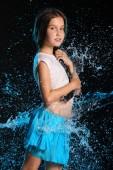 Portrét okouzlující dítě stojící s mokré štíhlé tělo. Hezká Mladá krásná dívka s holé břicho v mokré šaty a sukně. Atraktivní mladý teenager v tryskající vody.