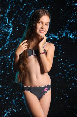 Portrait of a lovely little girl with slender body on a black. Pretty young beautiful child with bare belly posing in wet dark bikini. Attractive 12 years old teenager in splashes of water.