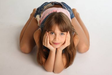 Beautiful girl in a denim shorts is resting on the floor barefoot. Elegant attractive child with a slender body and bare long legs. The young schoolgirl is 9 years old.