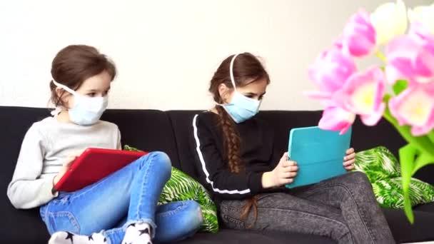 Online-Bildung, Fernunterricht, Hausaufgabenbetreuung. Kinder in medizinischer Maske lernen Hausaufgaben während des Online-Unterrichts zu Hause im digitalen Tablet oder Laptop. Soziale Distanz in Quarantäne. Selbstisolierung.