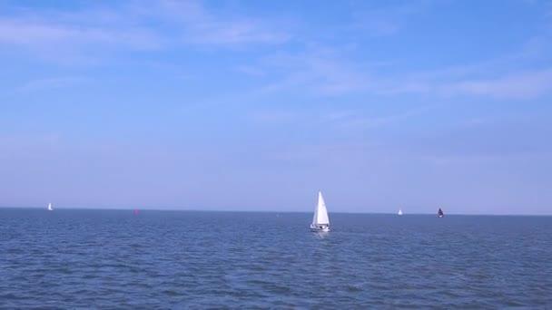 Jacht és csónak vitorlázás nyílt tengeren, napsütéses napokon. Raft Regatta vagy vitorlás verseny a tengeren. Vitorlás a láthatáron a gyönyörű óceánban. Sloops fehér vitorla alatt úszik a nyílt vízen.