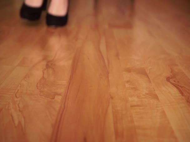 Ein Mädchen in schwarzen Schuhen lässt eine schwarze Perücke auf den Boden fallen. Das Konzept des Verkleidens