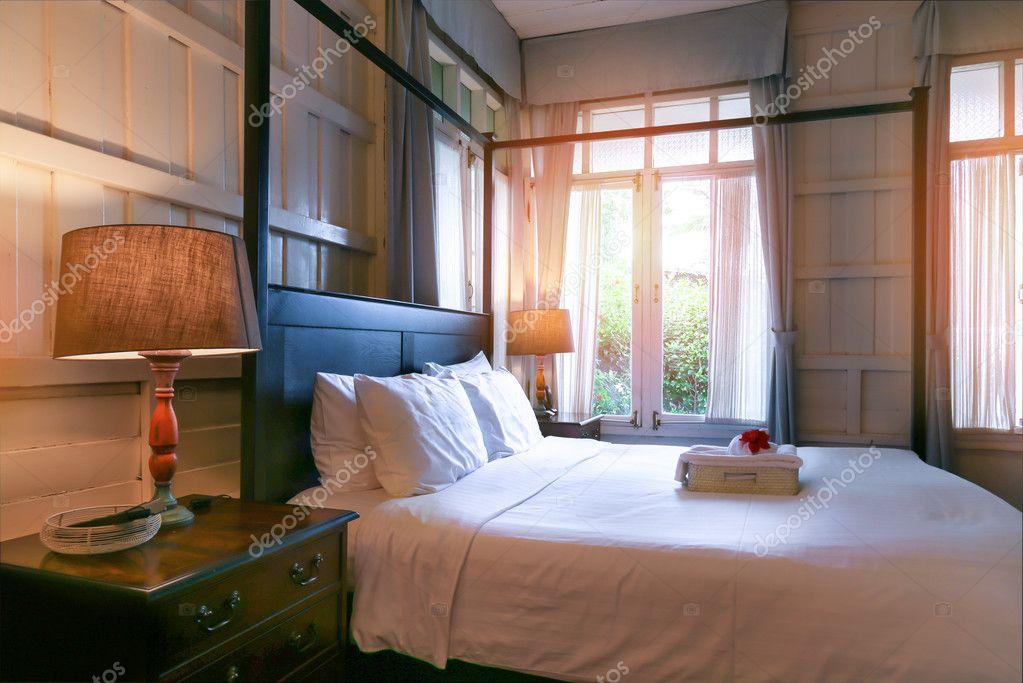 Interno accogliente camera da letto con cuscini e lampada da lettura ...