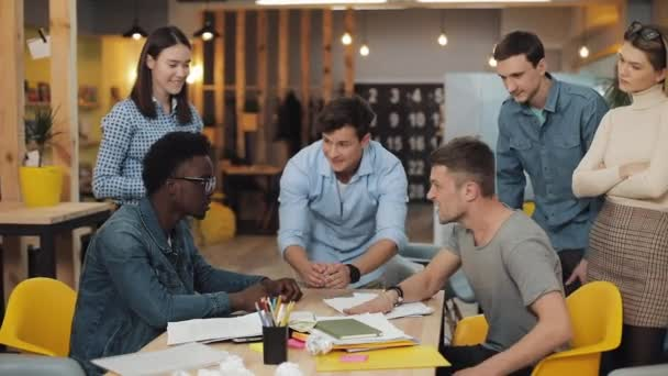 Két fiatal férfi küzd egymással az irodában. Vidám kollégák tapsolnak, nevetnek és szórakoznak.