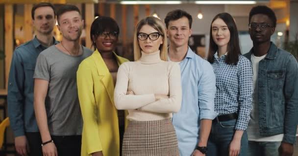 Portrét mladých obchodních lidí, kteří se usmívají a dívají se na kameru. Koncepce: internárodnost, spuštění, kariéra, úspěšný obchod, tým.