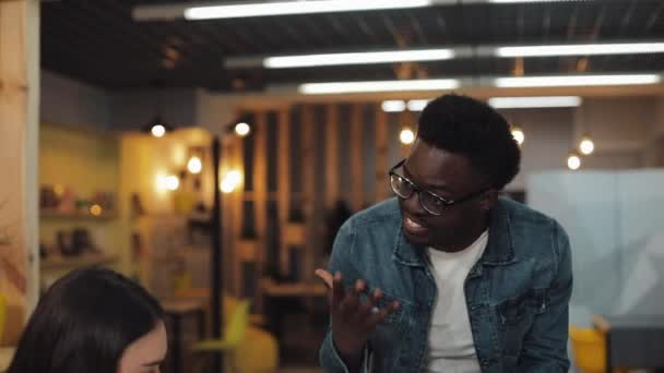 Angry african american business man screaming at colleagues during office meeting. Young multiracial group of people working in coworking space.