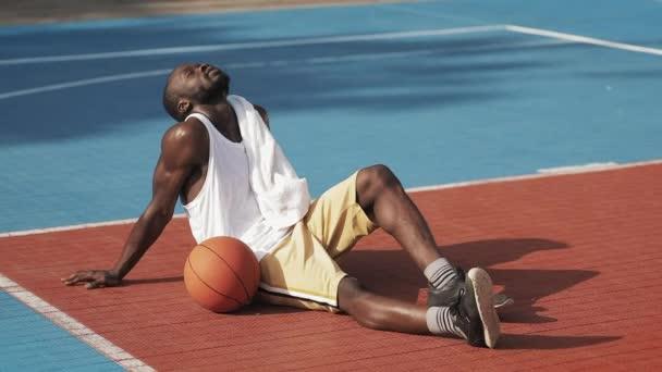 Mladý Musculy Handsome Afro American Guy sedí na zemi, vypadá unaveně, utírá tvář s ručníkem vestoje a pokračovat ve hře na Street Basketball Court.