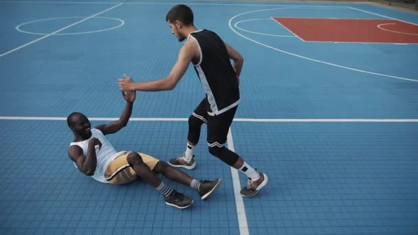 Mladý běloch kapky ruku a pomáhá vstát svalnatý afroameričan, který leží na ulici basketbalového hřiště. Zdravý životní styl a sportovní koncepce. Pomalý pohyb.