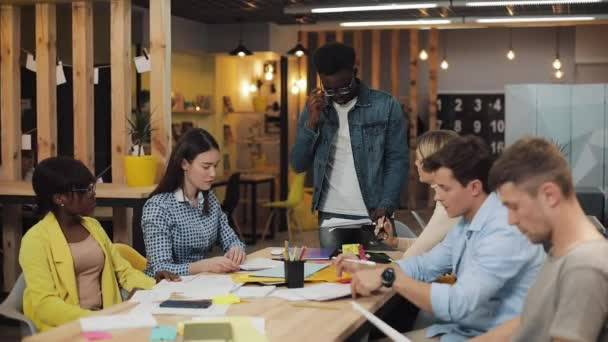 Dühös afro-amerikai üzletember kiabált a kollégáival az irodai megbeszélés alatt. Fiatal multiracionális csoport, akik coworking space-ben dolgoznak.