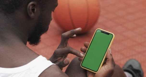 Back Side View of Young Bearded Afro American Guy Using his Smartphone, Touching and Scrooling the Screen while Seitting at Basketball Sport Ground. Koncept sportu a technologie. Zelená obrazovka.