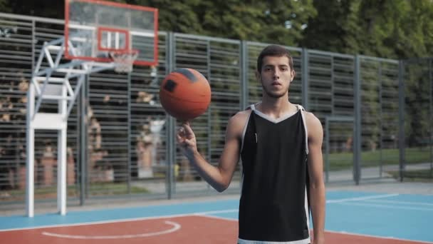 Young Caucasian Basketball Player Wearing Black Singlet Spinning the Ball on his Finger Standing at Street Basketbal Court and Looking to Camera. Healthy Lifestyle and Sport Concept.