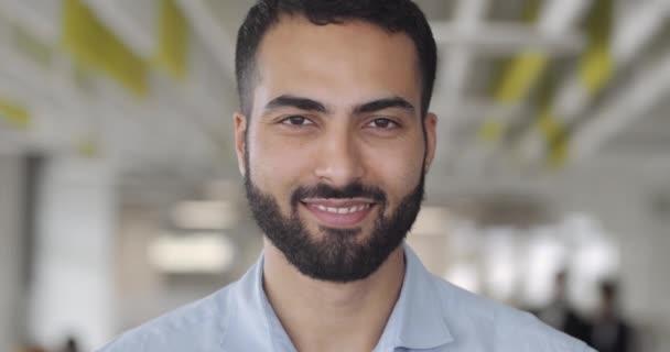 Közel egy mosolygó férfi irodai munkás, aki kamerába néz a Coworking zónában. Portré boldog ember startup alapító irodai szobában.Homályos háttér. Az emberek, a munka, az érzelmek fogalma.